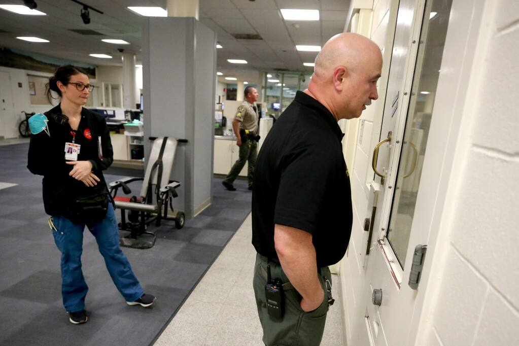 Sheriff's Office Correctional Lt. Don Huddleston and medical staff member Katie McGlothern, RN, communicate with an inmate in a negative-pressure cell about going to the hospital to be checked for COVID-19 after she developed a fever and had a potential exposure before her arrest. Photo taken in the booking area of the Sonoma County Main Adult Detention Facility in Santa Rosa on Sunday, March 15, 2020. (Beth Schlanker / The Press Democrat)