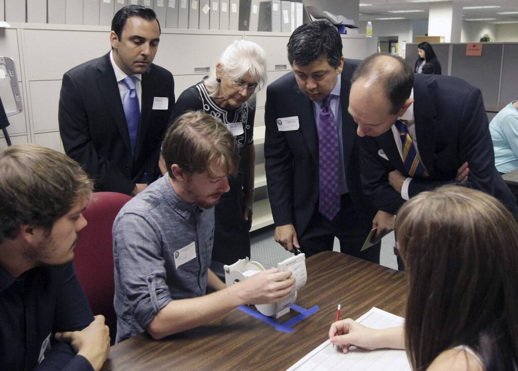 Observers watch as Micah Kagler of the Kern County elections division checks ballots in a recount of votes from the state controller race. (FELIX ADAMO / Bakersfield Californian)