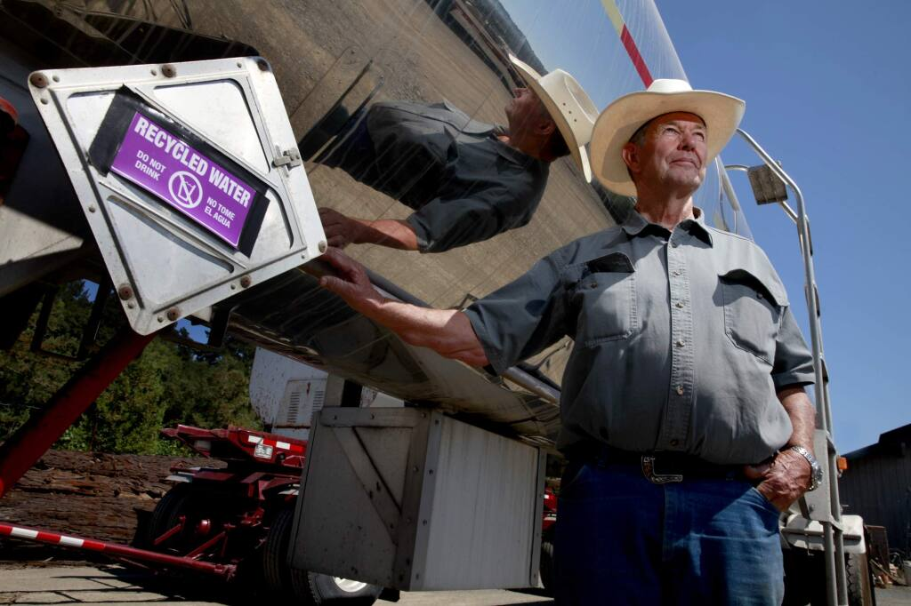 Richard Rued stands next to a water tanker truck that he uses to transport recycled water from the city of Healdsburg to irrigate his grapes at Rued Winery, on Thursday, Aug. 21, 2014. (BETH SCHLANKER / The Press Democrat)