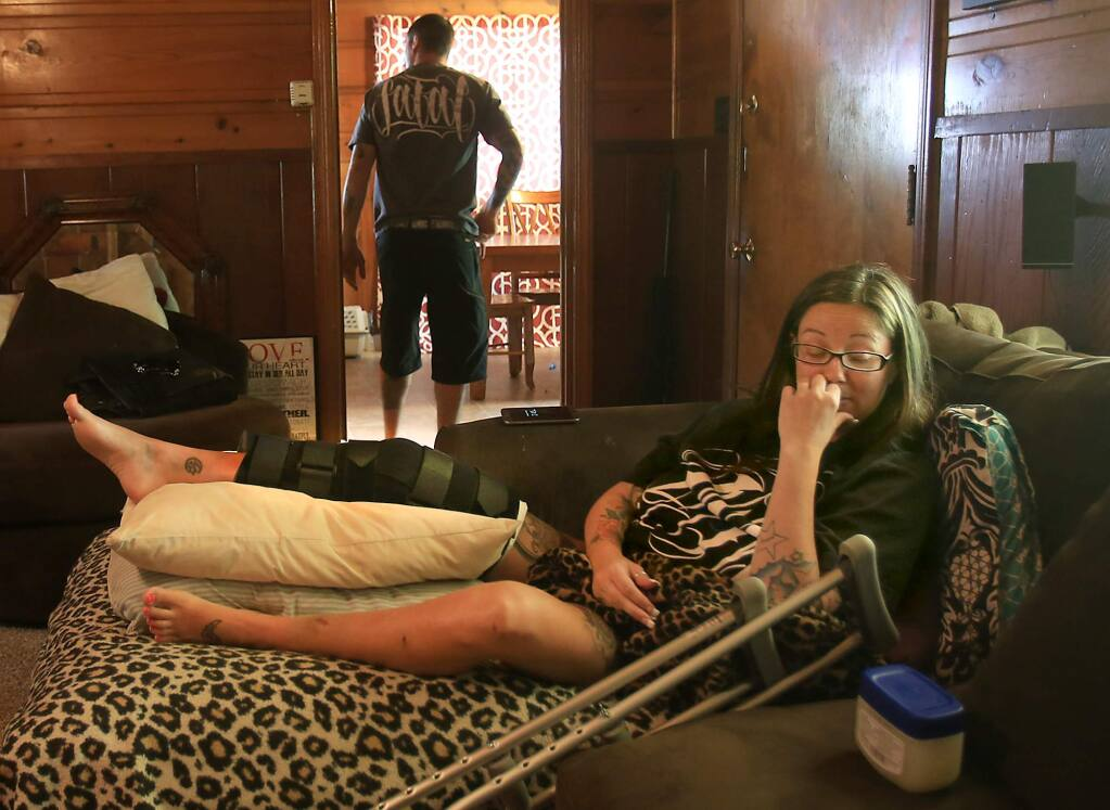 Heather Gladden rehabilitates at her home in Cloverdale, Tuesday April 19, 2016 after she fell about 500 feet when a zip line she was on outside Puerto Vallarta, Mexico failed, dropping her in to a canopy of trees. The accident occurred while she was on a cruise with her husband, Ryan, background. Her most serious injury was to her right knee and leg, which is in a brace. (Kent Porter / Press Democrat ) 2016