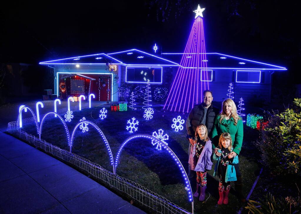 Nathan and Melissa Miller with their daughters Sawyer, 7, and Sloane, 6, stand in front of their home which is decorated with a high-tech holiday light display in Santa Rosa, California, on Tuesday, December 13, 2016. The Miller's holiday display features lights that are individually programmed to music, a digital banner that shows live text messages from visitors, and even a snow machine. (Alvin Jornada / The Press Democrat)