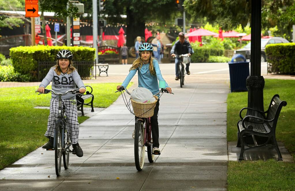 Julia Conley, 12, left, and Ella Holland, 12, rode their bikes to meet a friend at the town square in Healdsburg on Thursday, June 8, 2017. The town plans to launch a new bike sharing program for locals in a few months. (John Burgess/The Press Democrat)