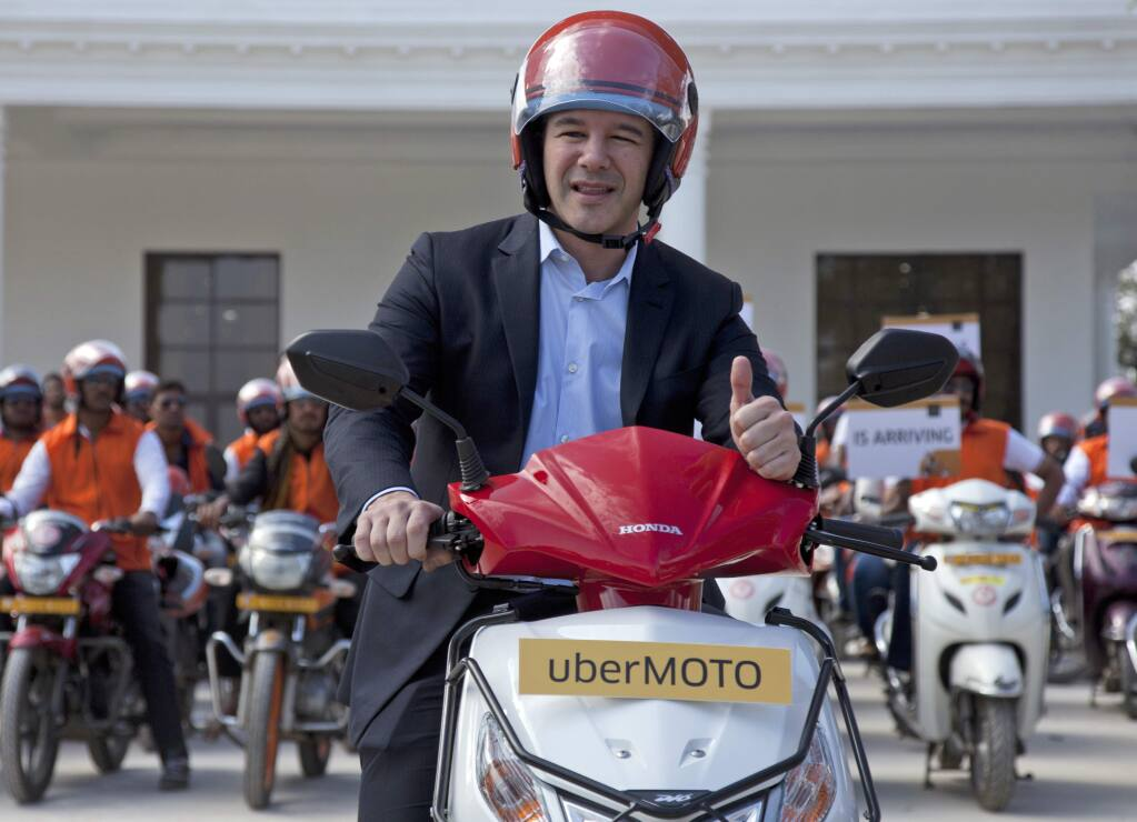 FILE - In this Dec. 13, 2016, file photo, Uber CEO Travis Kalanick, poses during the launch of its bike-sharing product, uberMOTO, in Hyderabad, India. Uber's CEO says he needs leadership help after a video has emerged of him arguing heatedly with a driver about fares. (AP Photo/Mahesh Kumar A., File)