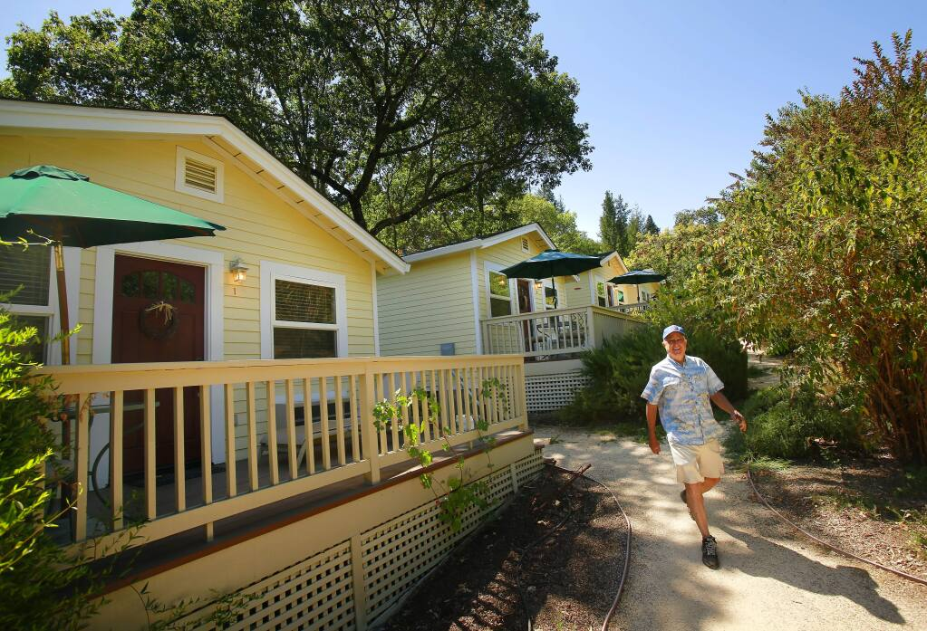 The owner of Aurora Park Cottages, Joe Hensley, walks by the trail around his six cottages for sale for a cost of $1.55 million in Calistoga on Friday, Aug. 8, 2014. (Conner Jay/The Press Democrat)
