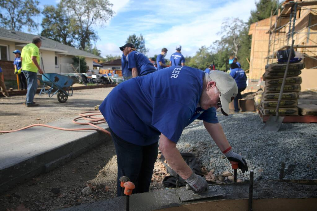 Linda Maule smooths out cement as she joins with volunteers working on three new single family homes on West Steele Lane as part of Habitat for Humanity's Raise the Roof campaign on Sunday, October 28, 2018 in Santa Rosa, California . (BETH SCHLANKER/The Press Democrat)