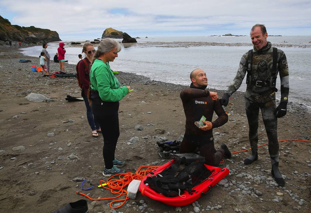 Billy Brown, center, gets a fist bump from his abalone dive instructor and guide Keith Peschel, right, while guide Leslie Russo walks him through properly tagging his abalone at Van Damme State Beach, in Little River on Monday, June 26, 2017. (Christopher Chung/ The Press Democrat)