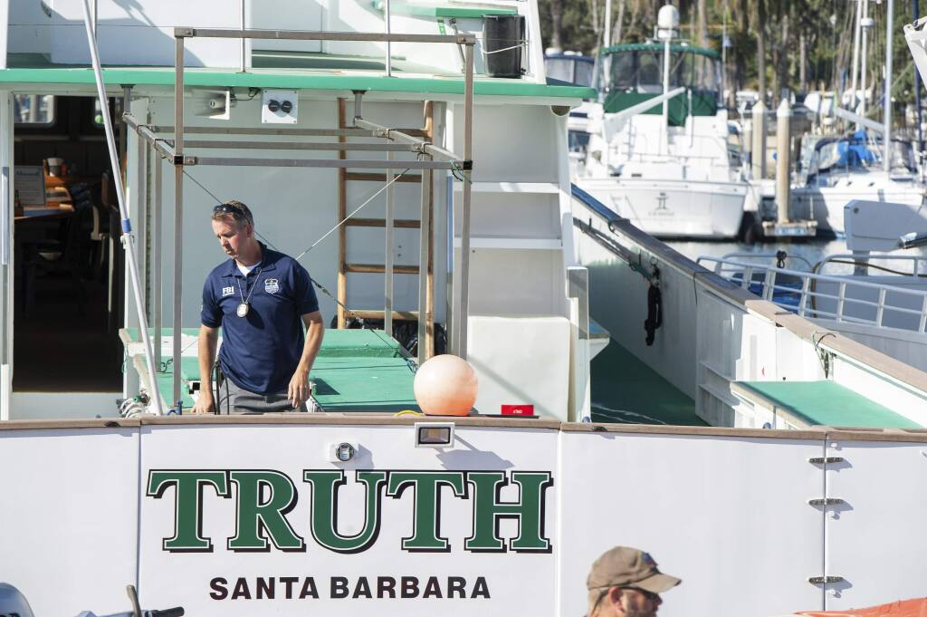 FBI agents search the Truth dive boat, a sister vessel to the Conception, as authorities issue a search warrant for the Truth Aquatics' offices on the Santa Barbara Harbor in Santa Barbara, Calif., Sunday, Sept. 8, 2019. The office was ringed in red 'crime scene' tape as more than a dozen agents took photos and carried out boxes. Thirty-four people died when the Conception burned and sank before dawn on Sept. 2. They were sleeping in a cramped bunkroom below the main deck and their escape routes were blocked by fire. (AP Photo/Christian Monterrosa)