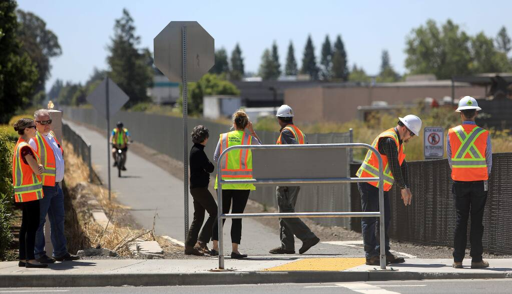 Personnel from SMART and Rohnert Park Public Works, Monday, July 1, 2019, gather on the sidewalk at Golf Course Drive and the SMART tracks, near the scene of the two deaths last Thursday and Friday of last week involving the commuter train at the intersection. (Kent Porter / The Press Democrat) 2019