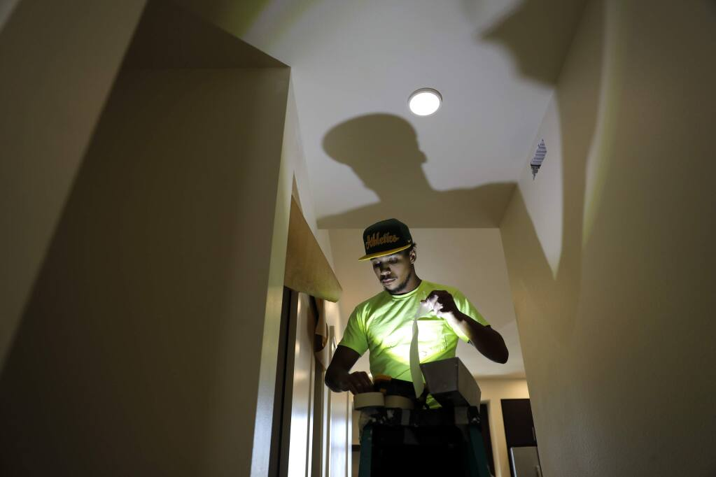Alexander Rominger of Katerra Construction does drywall finishing in a new unit of the Annadel apartment complex on Monday, April 30, 2018 in Santa Rosa, California . (BETH SCHLANKER/The Press Democrat)
