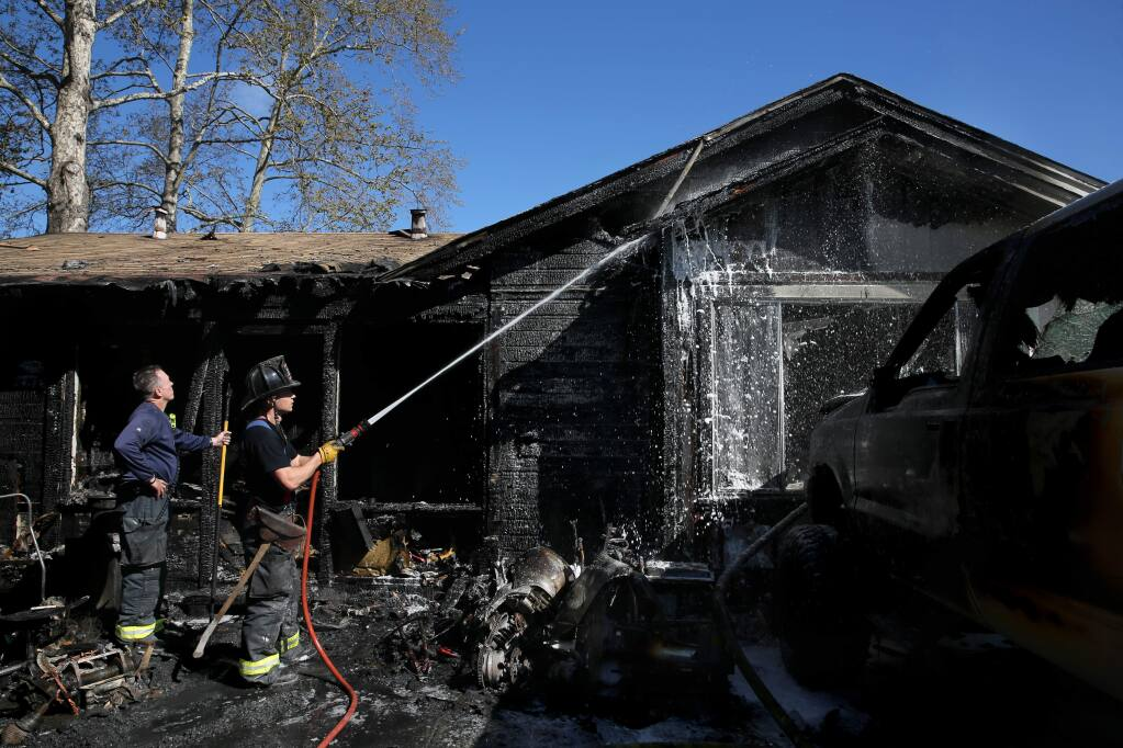 Santa Rosa Fire Captain Anthony Westergaard, left, and Engineer A.J. Alcocer try to put out a fire at 351 College Ave. in Santa Rosa on Sunday, March 31, 2019. (BETH SCHLANKER/ PD)