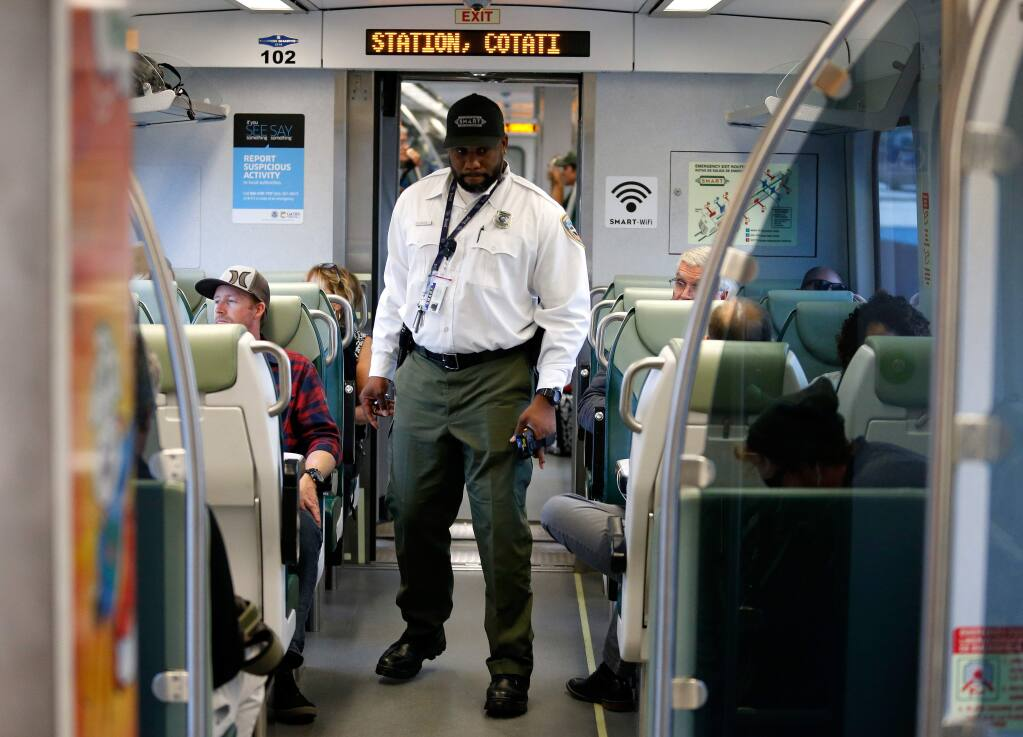SMART train conductor James Taylor walks through the cars as the train heads towards the station in Cotati, California, on Wednesday, September 20, 2017. (Alvin Jornada / The Press Democrat)