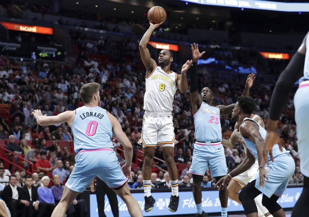 Golden State Warriors guard Alec Burks, center, shoots over Miami Heat forward Meyers Leonard (0) and guard Kendrick Nunn (25) during the first half, Friday, Nov. 29, 2019, in Miami. (AP Photo/Lynne Sladky)