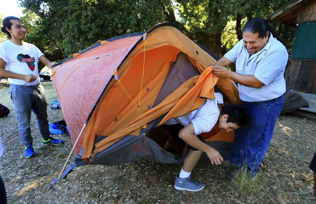 LandPaths Outreach and Diversity Director Omar Gallardo, right, holds the tent flap open for Christian Reyes while setting up camp with Enrique Farce Martinez, left, in the Inspired Forward program at the Bohemia Preserve in west Sonoma county. (JOHN BURGESS/The Press Democrat)