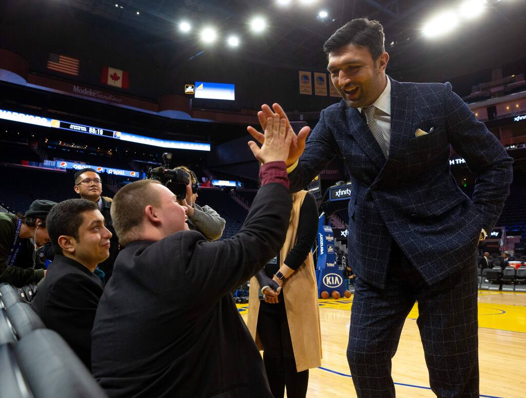 Basketball executive and former Golden State Warriors player Zaza Pachulia high-fives Austin Roach after chatting with him and Mauricio Stillman, far left, while they watch pregame warm ups a basketball game between the Indiana Pacers and Golden State Warriors at the Chase Center in San Francisco, California, on Friday, January 24, 2020. (Alvin Jornada / The Press Democrat)
