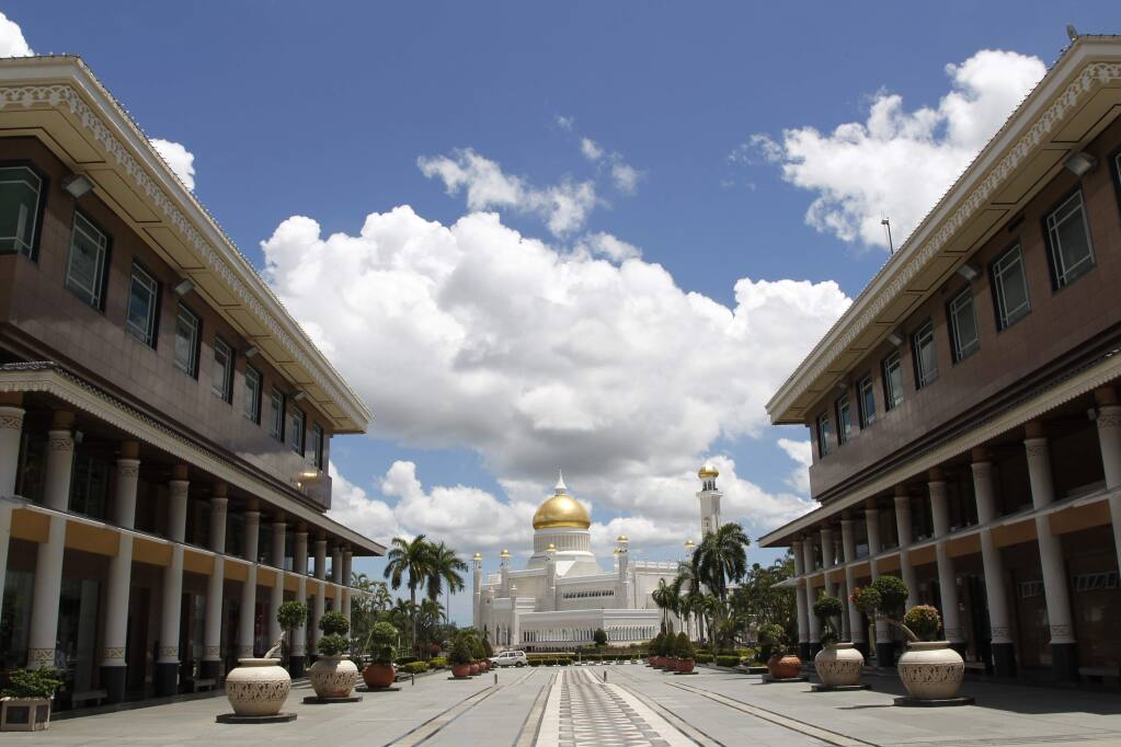In this April 23, 2013, photo, Sultan Omar Ali Saifuddien Mosque, one of the landmarks of Bandar Seri Begawan in Brunei. Brunei announced to implement Islamic criminal laws that punishes gay sex by stoning offenders to death. The legal change in the tiny, oil-rich monarchy, which also includes amputation for theft, is due to come into force Wednesday, April 3, 2019. (AP Photo/Vincent Thian)