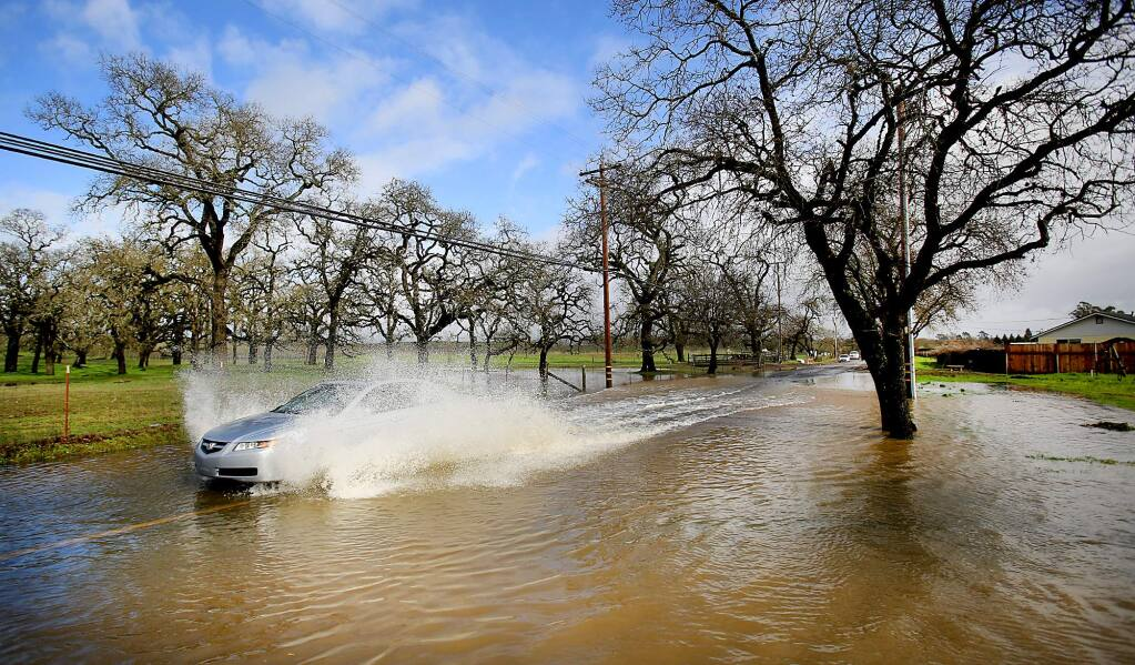 Piner Road in Santa Rosa becomes inundated after days of heavy rain, Tuesday Jan. 19, 2016, as storm drains are unable to handle the runoff from already saturated terrain. (Kent Porter / Press Democrat)