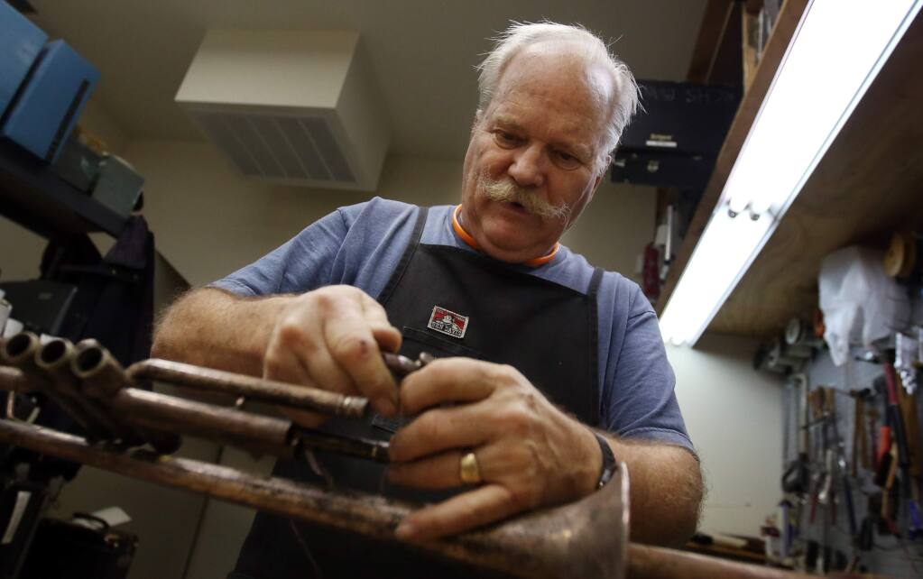 Bruce Blaikie works on a trumpet at Stanroy Music Center's new location on 4th Street in Santa Rosa, Thursday, November 20, 2014. (Crista Jeremiason / The Press Democrat)
