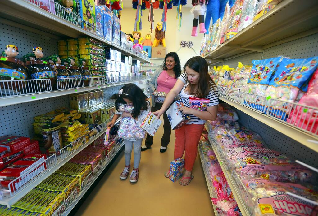 Monserrat Vargas, 7, collects bags of candy for her birthday pinata with her mother Azusena Chaparro, right, and Elva Alguilar at the Dulceria Las Tapatias in Santa Rosa. (Photo by John Burgess/The Press Democrat)