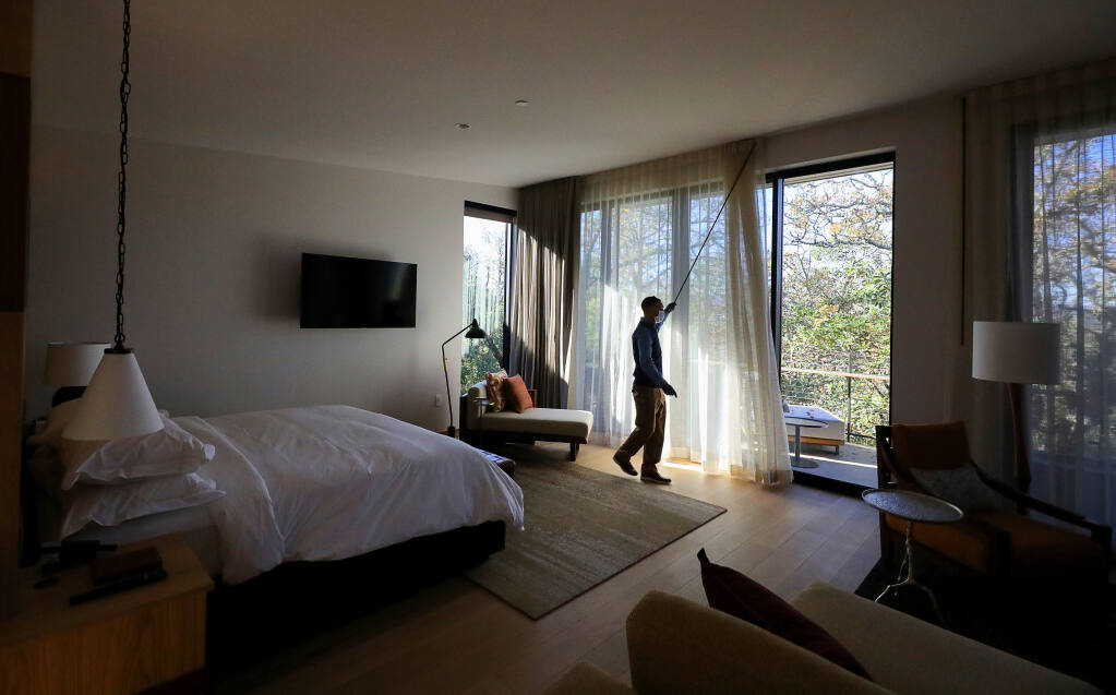 Quinn Reedy, guest services associate at Montage Healdsburg, opens the curtains of a deluxe studio room at the new luxury resort on the city's northern edge. (Christopher Chung / The Press Democrat) 2020