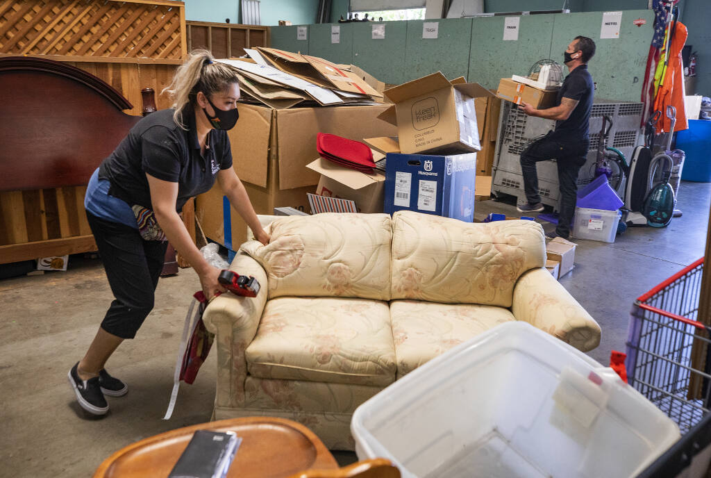 Marisol Mercato moves a piece of furniture that needs to be cleaned at the Redwood Gospel Mission Thrift Store in Santa Rosa. (John Burgess/The Press Democrat)