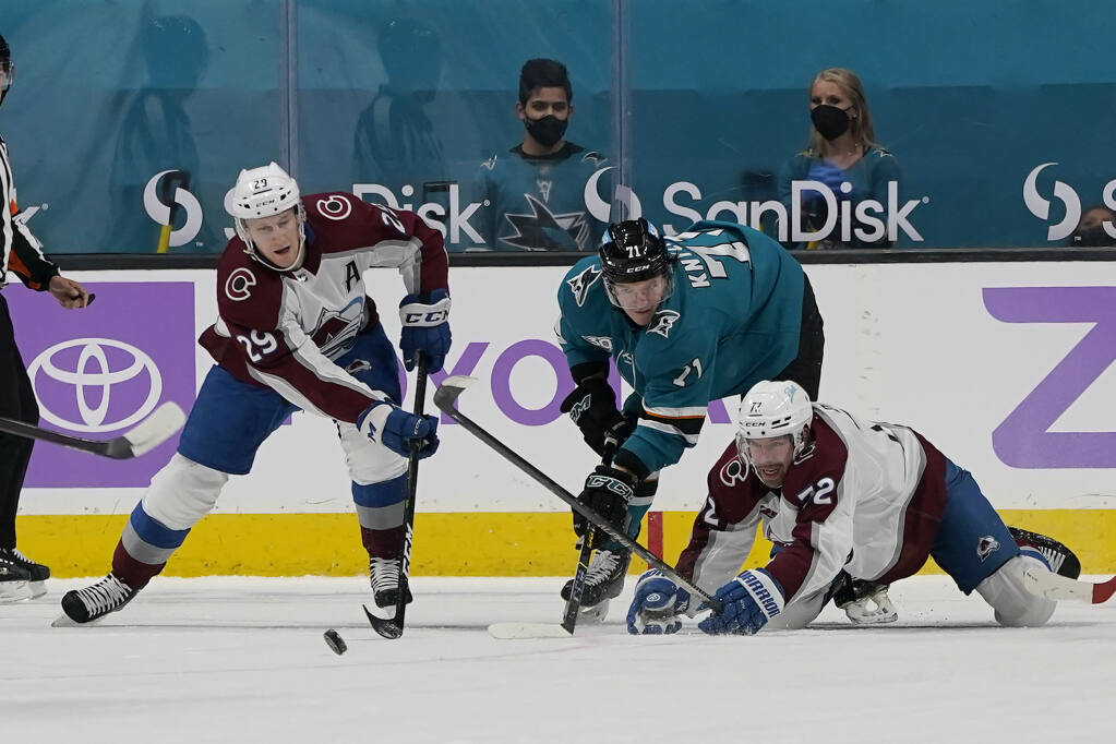 San Jose Sharks defenseman Nikolai Knyzhov, middle, looks toward the puck between Colorado Avalanche center Nathan MacKinnon, left, and Joonas Donskoi during the first period of an NHL hockey game in San Jose, Calif., Monday, May 3, 2021. (AP Photo/Jeff Chiu)