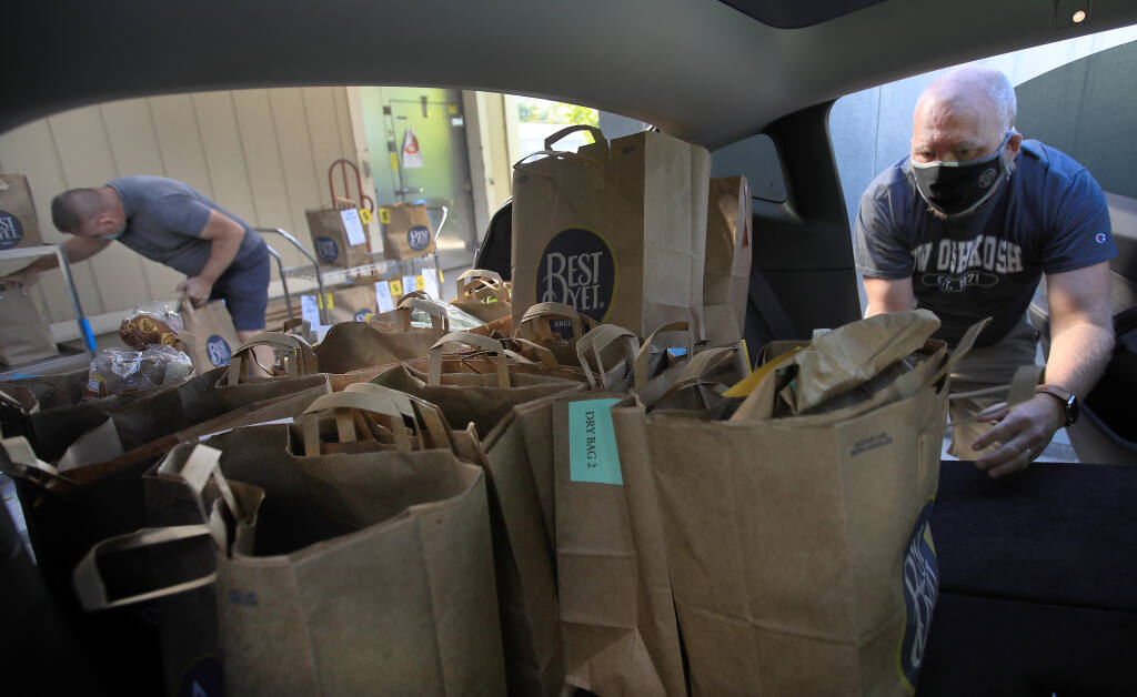 Preparing to make deliveries in Sonoma County, Dave Hendrickson of Sonoma, right, and Mike Bichanich of San Diego, load groceries in to Hendrickson's vehicle at Food For Thought in Forestville, Thursday, Oct. 29, 2020.  (Kent Porter / The Press Democrat)