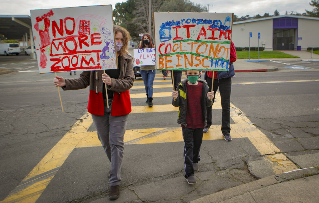 Karla Greschner and her son, Dean, 8, a second-grader at Old Adobe School, marched with other Petaluma students and parents to show their support for schools to reopen.(CRISSY PASCUAL/ARGUS-COURIER STAFF)