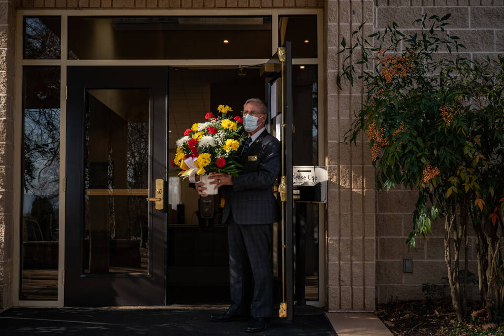 Ken Hammond, a funeral associate in Hagerstown, Maryland, holds flowers for the family of a man in his 50s who died of COVID-19 in January 2021. ( Salwan Georges / Washington Post)