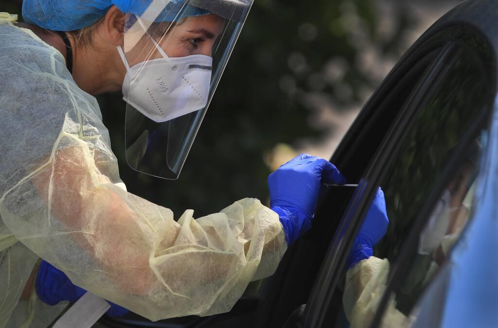 Paula Pelavin, a physicians assistant, obtains a swab sample during drive-up COVID-19 testing at Petaluma Health Center, Tuesday, July 14, 2020. (Kent Porter / The Press Democrat) 2020
