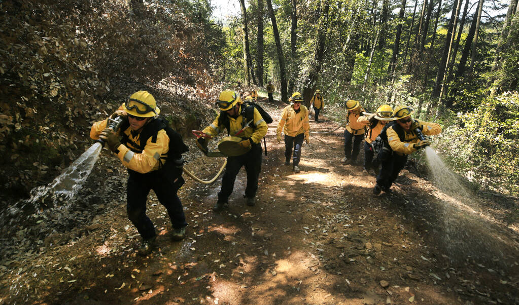 Sonoma County firefighter/paramedics, Rico Mendez, on left, with Andrew Negus; on right, Justin Pels, front and Eugene Stiponav, take part in wildland fire training on Tom Graham's property on St. Helena Road, Wednesday, May 5, 2021. September 2020's Glass fire burned about 12 acres of the property, left side of frame.  (Kent Porter / The Press Democrat) 2021