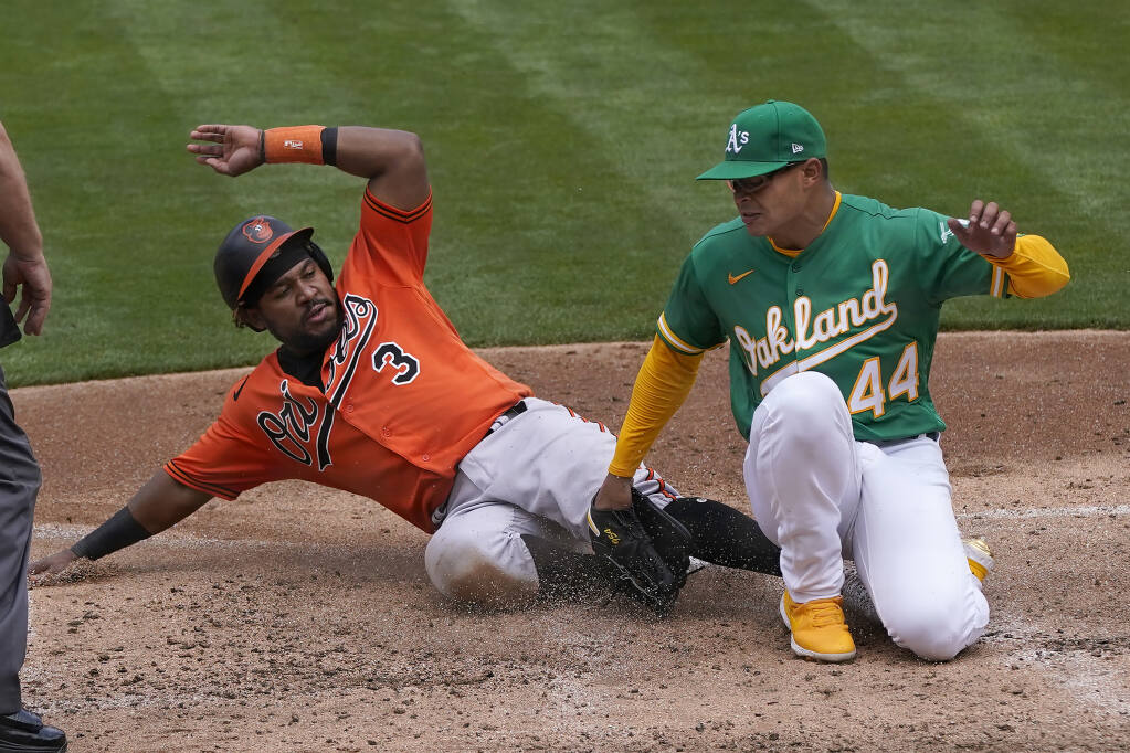 The Baltimore Orioles' Maikel Franco, left, slides home to score against Oakland Athletics pitcher Jesus Luzardo during the third inning in Oakland on Saturday, May 1, 2021. (Jeff Chiu / ASSOCIATED PRESS)