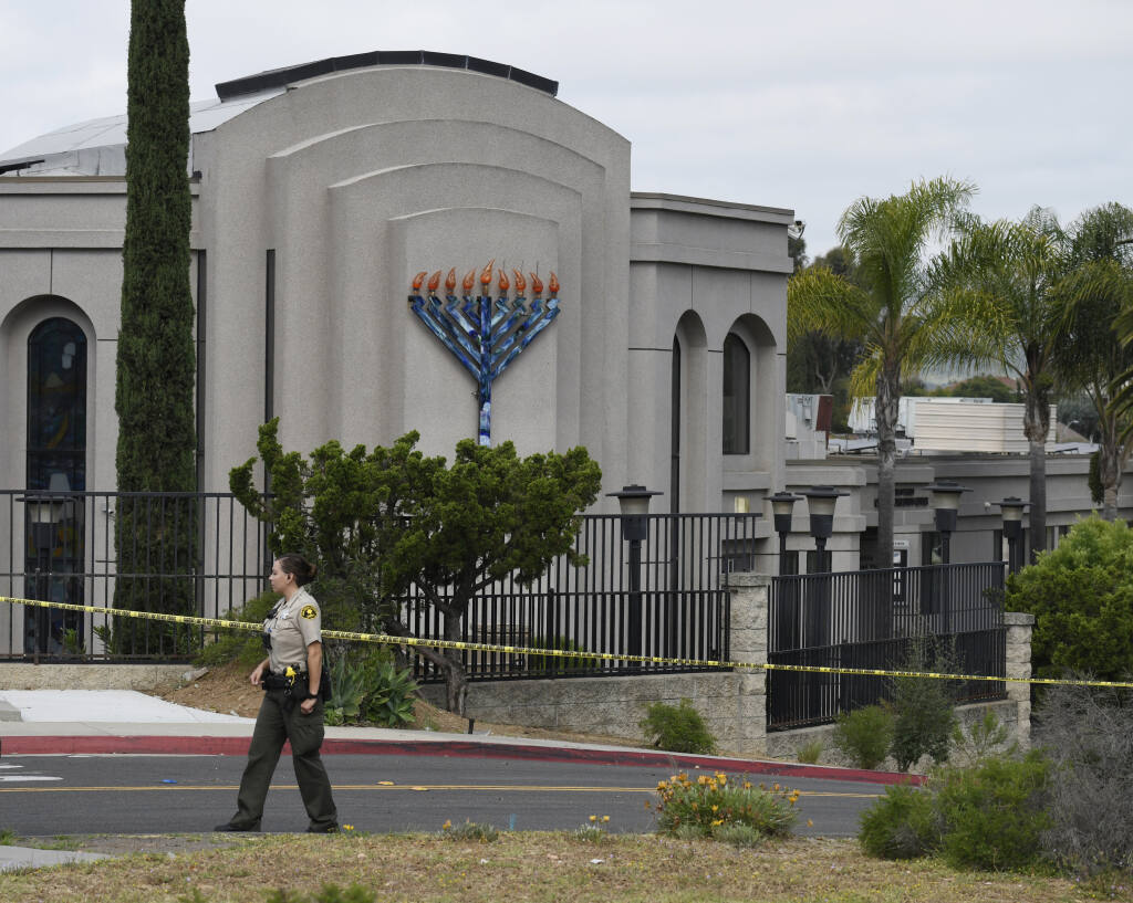 FILE - In this Sunday, April 28, 2019 file photo, a San Diego county sheriff's deputy stands in front of the Chabad of Poway synagogue, in Poway, Calif.  John T. Earnest pleaded guilty Tuesday, July 20, 2021, to murder and other charges in connection with a deadly shooting at a Southern California synagogue on the last day of Passover. (AP Photo/Denis Poroy, File)