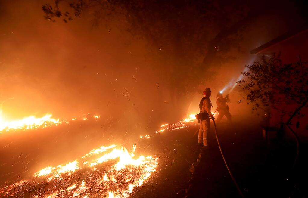 Cal Fire firefighters protect a structure at 1108 Bennett Lane and Highway 128 in Napa County close to the origin of the Tubbs fire on Sunday, Oct. 8, 2017. (KENT PORTER/ PD)