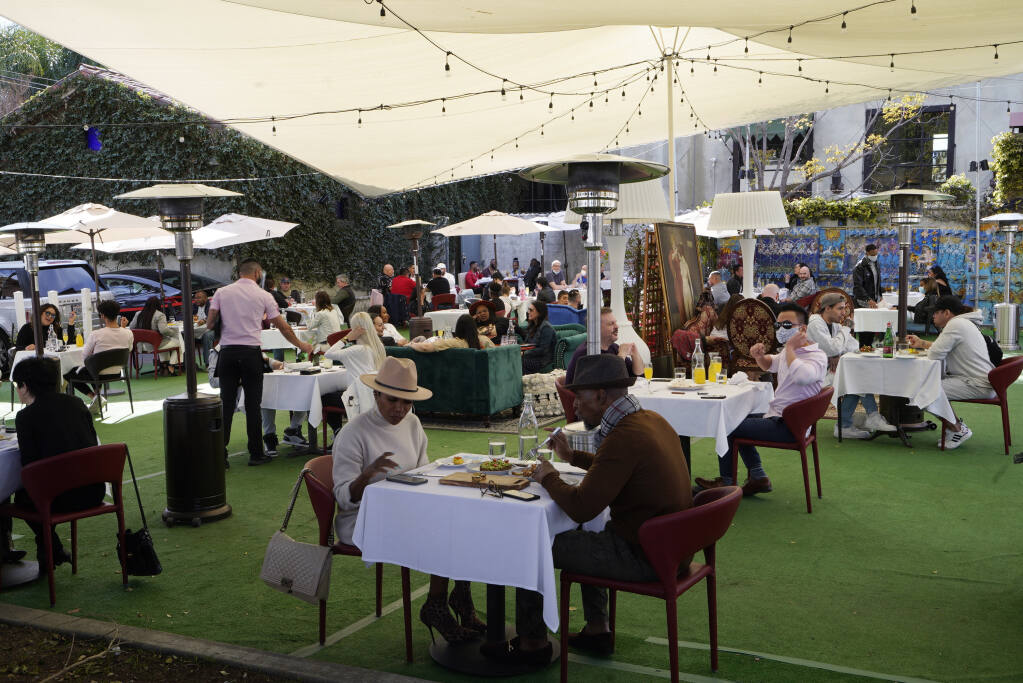 FILE - In this Feb. 14, 2021, file photo, people dine under a tent outside a restaurant in West Hollywood, Calif.  (AP Photo/Damian Dovarganes, File)