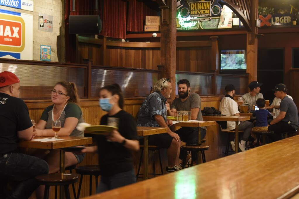 Guests seating is divided by empty tables to provide social distancing in the bar area at Russian River Brewing Company in downtown Santa Rosa, Calif., on Thursday, July 2, 2020. (Erik Castro/For The Press Democrat)