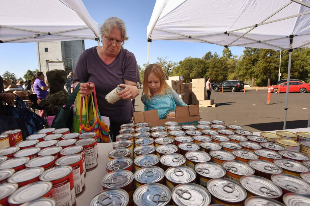 'We were camped out at Goat Rock for three nights, and it was freezing,' said Nicole La Rochelle of Monte Rio, who was collecting donated food for herself, and for her friend's daughter Aiona Lewis, 6, right, Friday, Nov. 1, 2019, at the Santa Rosa Fire Department Training Tower. (Erik Castro/for The Press Democrat)