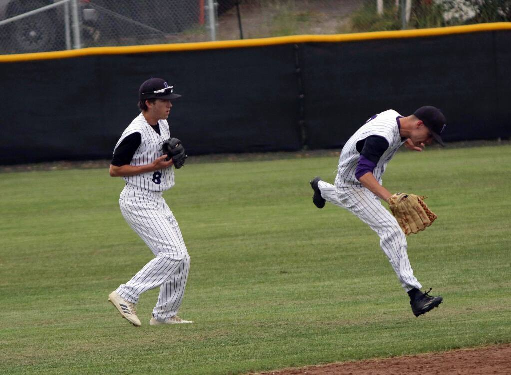 DWIGHT SUGIOKA/FOR THE ARGUS-COURIERPetaluma outfielders Sam Jacobs and Kempton Brandis chase down the ball in the Trojans' NCS game against El Cerrito.