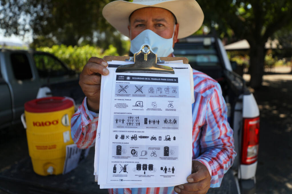 Enterprise Vineyards, Inc., field supervisor Miguel Santoyo holds up the guidelines that he reads to all of his workers at the start of each day, in Kenwood on Tuesday, July 28, 2020.  All Enterprise Vineyards, Inc., field workers wear face masks and all machinery is disinfected after use.(Christopher Chung/ The Press Democrat)