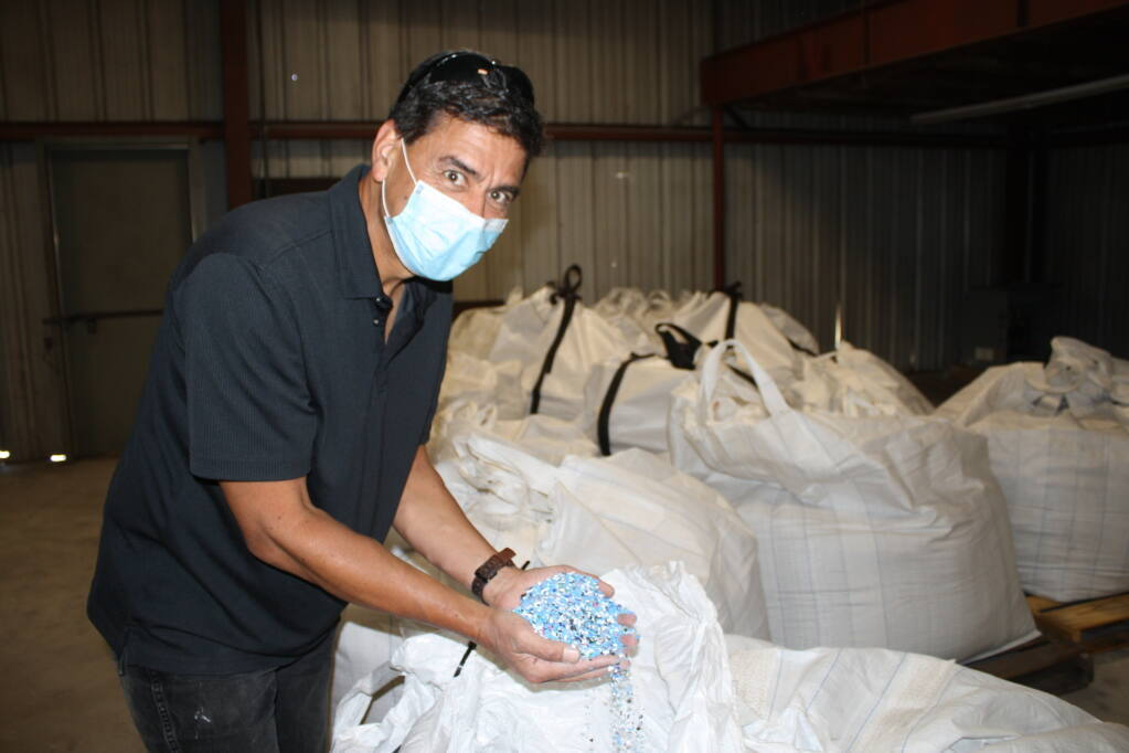 Brian Bauer, CEO of Reysnergi, Inc., holds handfuls of chips shredded from ocean waste plastic debris ready for reprocessing into diesel fuel or to be used to produce new plastic products. (courtesy photo)