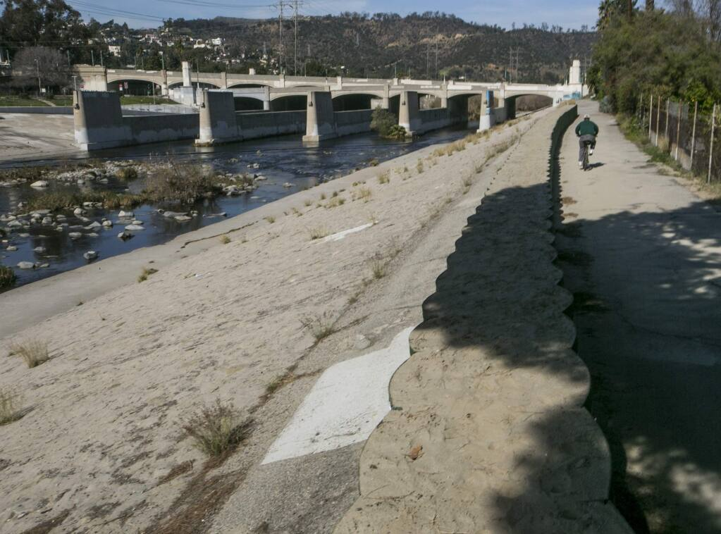 FILE - In this Feb. 12, 2016 file photo, a cyclist rides along recently installed temporary flood control walls along the low level L.A. River in Los Angeles. The US Army Corps of Engineers had installed about three miles of temporary barriers along the river through Griffith Park, Atwater Village, and Silver Lake, to increase the amount of water the river can hold during El Nino season. Members of the state Water Resources Control Board are scheduled to decide Tuesday, Feb. 20, 2018, whether to bring back what had been temporary water bans from California's 2013-2017 drought, and make them permanent. (AP Photo/Damian Dovarganes, File)