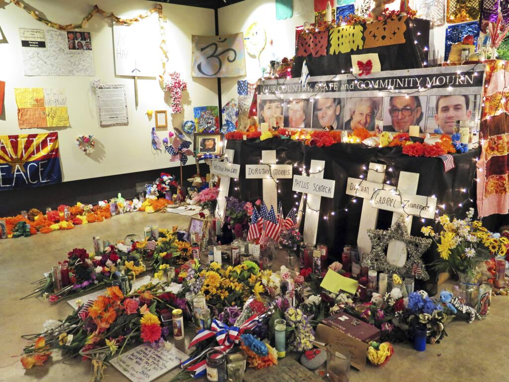 FILE - In this Jan. 9, 2015, file photo, flowers, teddy bears and inspirational posters line a room at the Arizona History Museum in Tucson, Ariz. The items were left at the scene of the Jan. 8, 2011, shooting in Tucson that left several dead and over a dozen wounded. Survivors of the Tucson mass shooting that left former U.S. Rep. Gabby Giffords severely wounded are pleading with the public to help pay for a long-planned memorial after state funding fell through during this year's Legislative session. (AP Photo/Astrid Galvan, File)