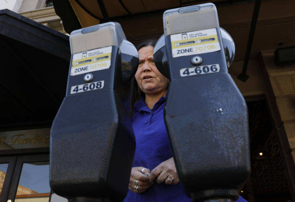 Bev Barron puts money into the meter on Fourth St. in Santa Rosa on Monday, March 18, 2019. (BETH SCHLANKER/ The Press Democrat)