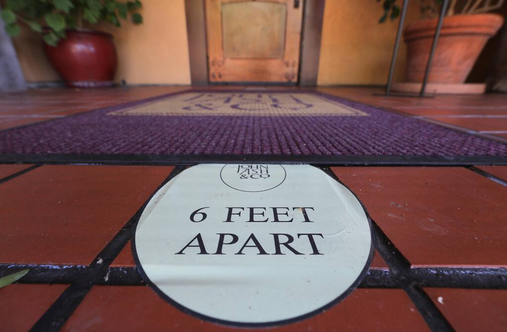 A social distancing sticker reminds guests at John Ash & Co., at Vintners Resort, to stay six feet apart in Santa Rosa on Friday, June 26, 2020.  (Christopher Chung/ The Press Democrat)