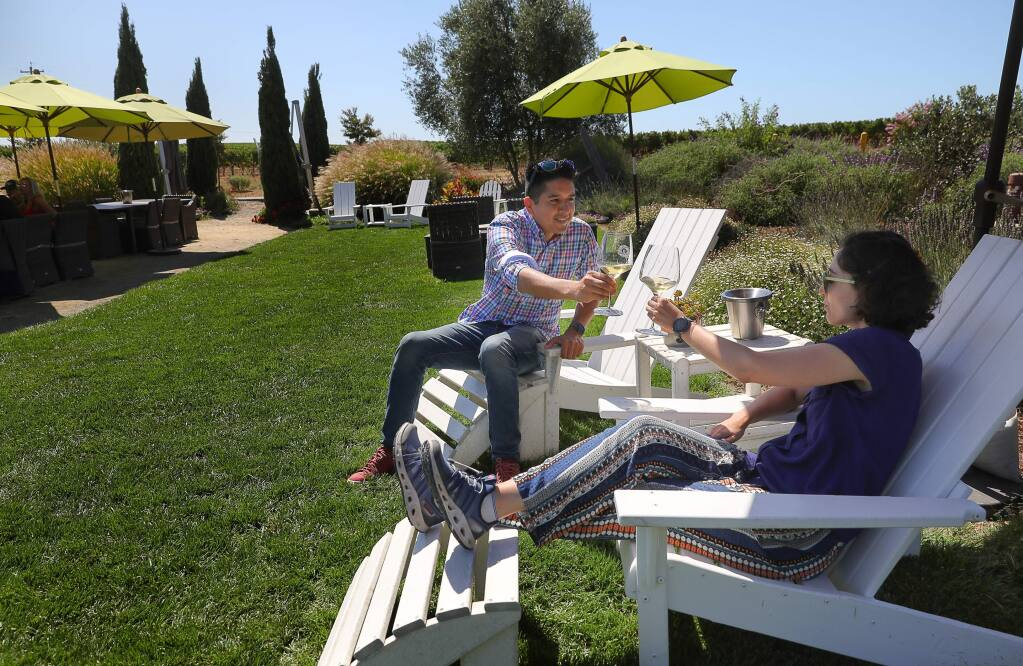 Oscar Patino, left, and Rachel Greif, enjoy a glass of wine at Bouchaine Vineyards, near Napa, during a stop on a vegan tour with La Belle Vie Tours on Friday, August 30, 2019. (Christopher Chung/ The Press Democrat)