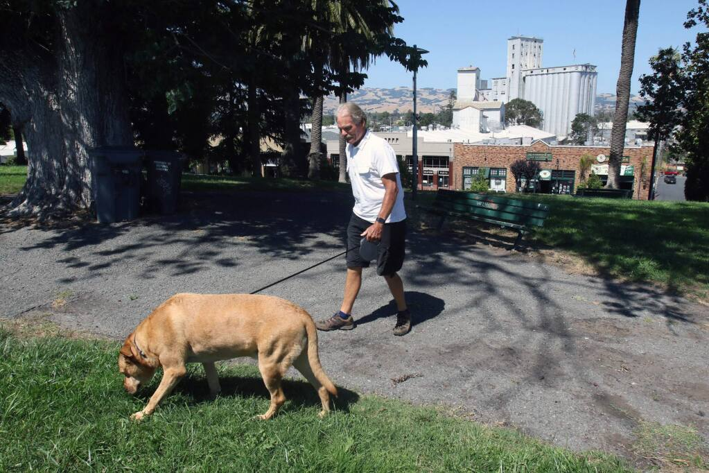 Retired Petaluma fireman Dennis Noreil wlaks his dog Leo in Penry Park in Petaluma on Monday afternoon July 3, 2017. Scott Manchester/For The Argus-Courier
