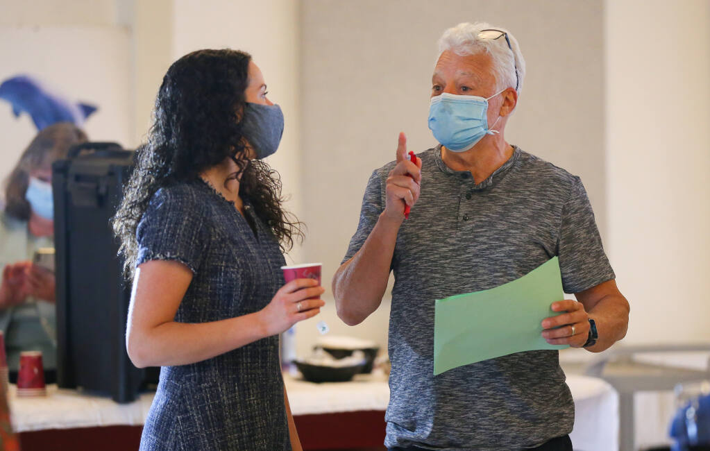 Alexandria Sarovich, left, and Daryl Groom talk during the North Coast Wine Challenge in Santa Rosa on Tuesday, April 6, 2021.  (Christopher Chung / The Press Democrat)