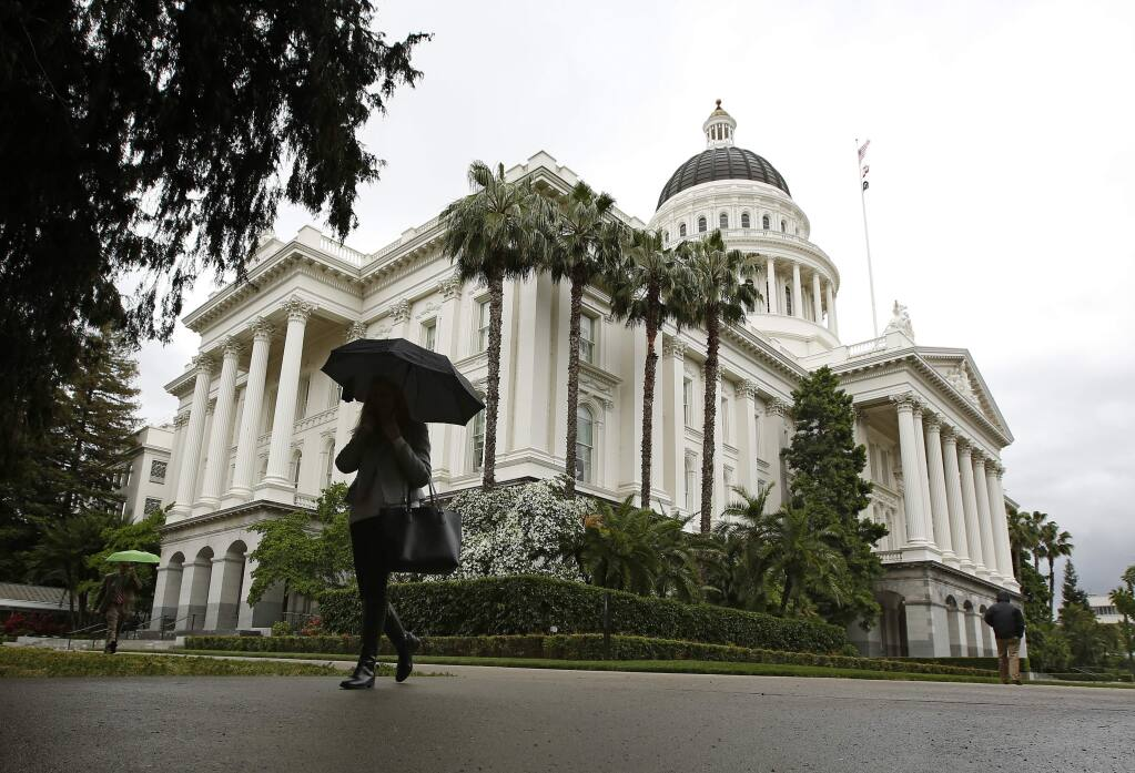 FILE - In this May 16, 2019 file photo a pedestrian walks by the State Capitol, in Sacramento, Calif. California lawmakers will return to work for the second half of their two-year session. Gov. Gavin Newsom must present his budget proposal to lawmakers by Friday, Jan.10, 2020. Lawmakers in the Senate and Assembly have until Jan. 31 to act on bills that were carried over from last year. Democrats have comfortable majorities in both chambers. Democratic leaders say they plan to focus this year on combating homelessness, protecting the environment and mitigating impacts from wildfires. (AP Photo/Rich Pedroncelli,File)