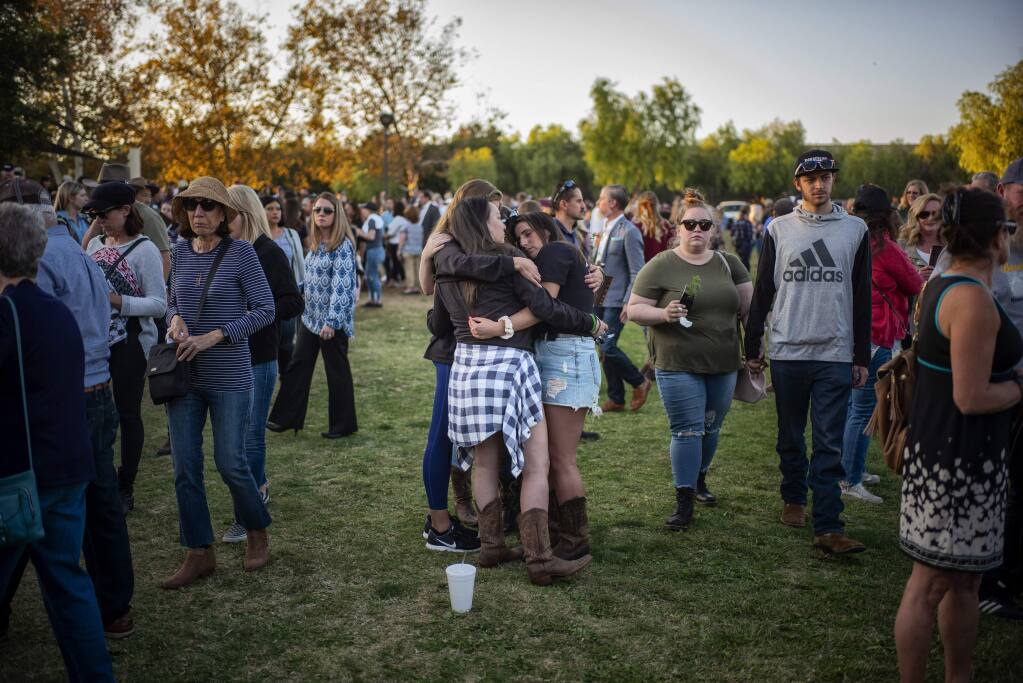 People comfort one another during the dedication of the Borderline Healing Garden at Conejo Creek Park in Thousand Oaks, Calif., Thursday, Nov. 7, 2019. The dedication marked the anniversary of a fatal mass shooting at a country-western bar a year earlier. (Hans Gutknecht/The Orange County Register via AP)