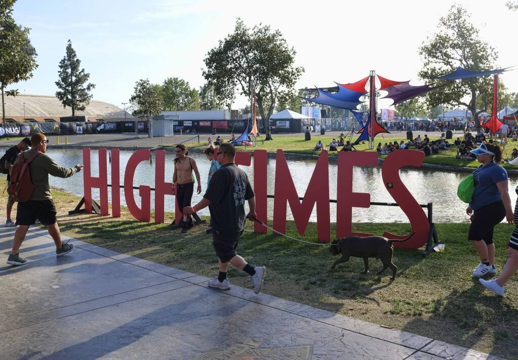 FILE - In this Sunday, April 23, 2017, file photo, visitors arrive at the fairgrounds to attend the High Times Cannabis Cup in San Bernardino, Calif. The owner of High Times is going to start selling marijuana after championing its use in the pages of its magazine for nearly half a century. Hightimes Holding Corp. said Tuesday, April 28, 2020 is acquiring 13 dispensaries from Harvest Health and Recreation, one of the largest multi-state producers and sellers of cannabis in the U.S. (AP Photo/Richard Vogel, File)