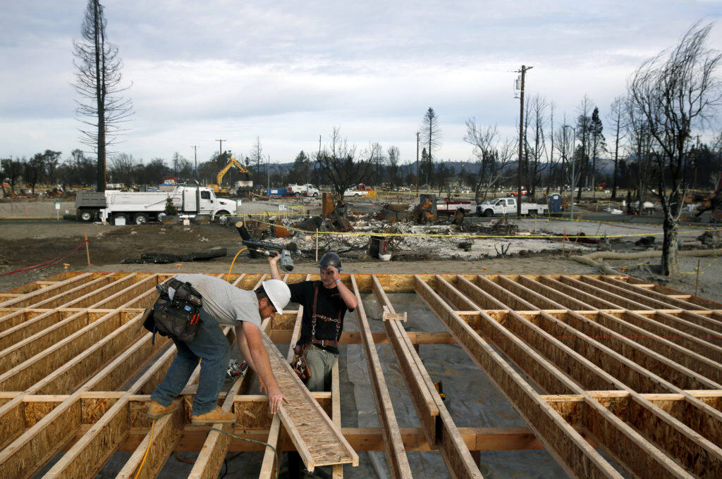 Jesse Merritt, left, and Joey Horst with Lake County Contractors install floor joists as they rebuild a home on Kerry Lane in Coffey Park in Santa Rosa, on Tuesday, January 2, 2018. (BETH SCHLANKER/ The Press Democrat)